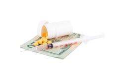 Ταμπλέτες και σύριγγα σε έναν αμερικανικό λογαριασμό δολαρίων που απομονώνεται στο λευκό Στοκ Εικόνες