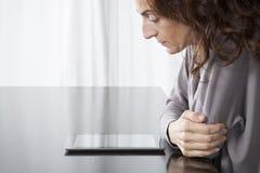 Ταμπλέτα ανάγνωσης γυναικών στον πίνακα Στοκ Εικόνες