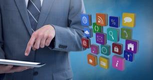 Ταμπλέτα εκμετάλλευσης επιχειρηματιών με τα εικονίδια apps με το μπλε ομιχλώδες υπόβαθρο Στοκ φωτογραφίες με δικαίωμα ελεύθερης χρήσης