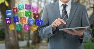 Ταμπλέτα εκμετάλλευσης επιχειρηματιών με τα εικονίδια apps στην πορεία με τα δέντρα Στοκ φωτογραφία με δικαίωμα ελεύθερης χρήσης