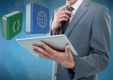 Ταμπλέτα εκμετάλλευσης επιχειρηματιών με τα εικονίδια apps στο μπλε ομιχλώδες κλίμα Στοκ φωτογραφία με δικαίωμα ελεύθερης χρήσης