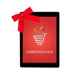 Ταμπλέτα με το κόκκινες τόξο δώρων και την πώληση Χριστουγέννων σε μια οθόνη Στοκ Φωτογραφία