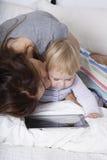 Ταμπλέτα προσοχής μωρών φιλήματος μητέρων Στοκ φωτογραφίες με δικαίωμα ελεύθερης χρήσης