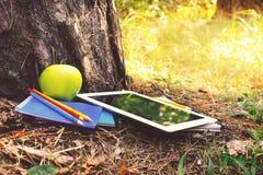 Ταμπλέτα, σημειωματάρια, μολύβια, μήλο στο πάρκο στο φως θερινού ηλιοβασιλέματος στοκ εικόνα