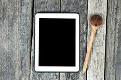 Ταμπλέτα στην ξύλινη επιφάνεια και το ξύλινο κουτάλι Στοκ Εικόνες