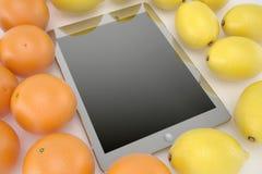 Ταμπλέτα στο άσπρο υπόβαθρο με τα πορτοκάλια και τα λεμόνια Στοκ φωτογραφία με δικαίωμα ελεύθερης χρήσης