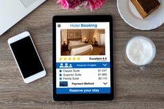 Ταμπλέτα υπολογιστών με app τον τηλεφωνικό πίνακα κράτησης και αφής ξενοδοχείων στοκ εικόνα