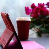 Ταμπλέτα, φλιτζάνι του καφέ και λουλούδια Στοκ εικόνα με δικαίωμα ελεύθερης χρήσης