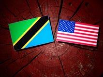 Τανζανική σημαία με την ΑΜΕΡΙΚΑΝΙΚΗ σημαία σε ένα κολόβωμα δέντρων Στοκ Φωτογραφίες