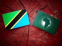 Τανζανική σημαία με την αφρικανική σημαία ένωσης σε ένα κολόβωμα δέντρων Στοκ φωτογραφίες με δικαίωμα ελεύθερης χρήσης