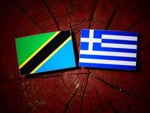 Τανζανική σημαία με την ελληνική σημαία σε ένα κολόβωμα δέντρων που απομονώνεται Στοκ φωτογραφίες με δικαίωμα ελεύθερης χρήσης