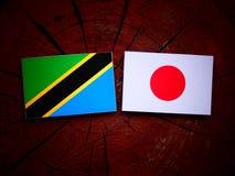 Τανζανική σημαία με την ιαπωνική σημαία σε ένα κολόβωμα δέντρων που απομονώνεται Στοκ Φωτογραφίες