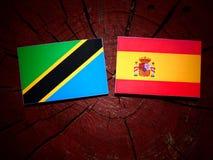Τανζανική σημαία με την ισπανική σημαία σε ένα κολόβωμα δέντρων Στοκ Φωτογραφίες
