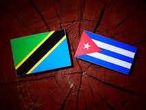 Τανζανική σημαία με την κουβανική σημαία σε ένα κολόβωμα δέντρων που απομονώνεται Στοκ Φωτογραφία