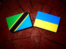 Τανζανική σημαία με την ουκρανική σημαία σε ένα κολόβωμα δέντρων που απομονώνεται Στοκ Φωτογραφία