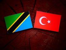 Τανζανική σημαία με την τουρκική σημαία σε ένα κολόβωμα δέντρων Στοκ Εικόνες