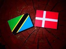 Τανζανική σημαία με τη δανική σημαία σε ένα κολόβωμα δέντρων που απομονώνεται Στοκ Εικόνες