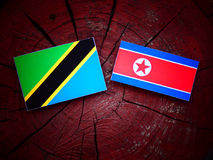 Τανζανική σημαία με τη βόρεια κορεατική σημαία σε ένα κολόβωμα δέντρων Στοκ Εικόνες