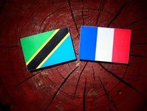 Τανζανική σημαία με τη γαλλική σημαία σε ένα κολόβωμα δέντρων που απομονώνεται Στοκ εικόνες με δικαίωμα ελεύθερης χρήσης