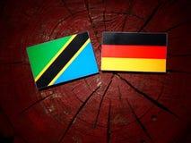 Τανζανική σημαία με τη γερμανική σημαία σε ένα κολόβωμα δέντρων Στοκ Εικόνες