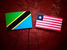 Τανζανική σημαία με τη λιβεριανή σημαία σε ένα κολόβωμα δέντρων που απομονώνεται Στοκ Εικόνες