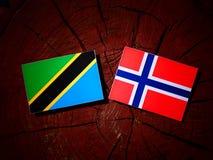 Τανζανική σημαία με τη νορβηγική σημαία σε ένα κολόβωμα δέντρων που απομονώνεται Στοκ Φωτογραφία