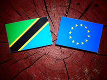 Τανζανική σημαία με τη σημαία της ΕΕ σε ένα κολόβωμα δέντρων που απομονώνεται Στοκ Φωτογραφία