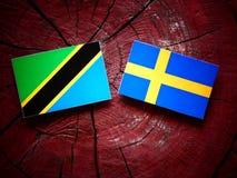 Τανζανική σημαία με τη σουηδική σημαία σε ένα κολόβωμα δέντρων Στοκ Εικόνες