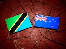 Τανζανική σημαία με τη σημαία της Νέας Ζηλανδίας σε ένα κολόβωμα δέντρων που απομονώνεται Στοκ φωτογραφίες με δικαίωμα ελεύθερης χρήσης