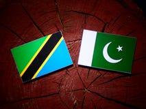 Τανζανική σημαία με τη σημαία του Πακιστάν σε ένα κολόβωμα δέντρων που απομονώνεται Στοκ Φωτογραφία