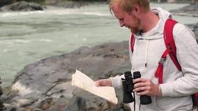 Ταξίδια ατόμων στα βουνά ο τουρίστας με το χάρτη και τις διόπτρες ψάχνει τον τρόπο στα βουνά τουρίστας που αποκτάται νέος απόθεμα βίντεο
