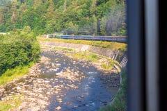 Ταξίδι, άποψη υπολοίπου από το παράθυρο τραίνων στο γύρισμα του τραίνου, ποταμός και δέντρα Οριζόντιο πλαίσιο Στοκ φωτογραφία με δικαίωμα ελεύθερης χρήσης