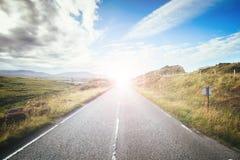 Ταξίδι ή περιπέτεια: Εγκαταλειμμένος, ειδυλλιακός δρόμος στη Σκωτία, νησί της Skye Φωτεινή ηλιαχτίδα στοκ εικόνες