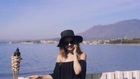 Ταξίδι γυναικών που μιλά στο τηλέφωνο, χαριτωμένο χαμόγελο κοριτσιών, στο υπόβαθρο της θάλασσας/του ωκεανού Η έννοια της σύνδεσης απόθεμα βίντεο