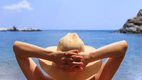 Ταξίδι, κλίση, έννοια διακοπών Η γυναίκα στο καπέλο βρίσκεται στο deckchair στην παραλία θαλασσίως στοκ φωτογραφία με δικαίωμα ελεύθερης χρήσης