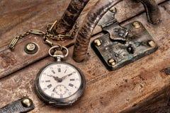 Ταξίδι με το ρολόι τσεπών αρχαίο σε μια γρατσουνισμένη βαλίτσα δέρματος στο σταθμό τρένου, έτοιμο για την αναχώρηση ελεύθερη απεικόνιση δικαιώματος