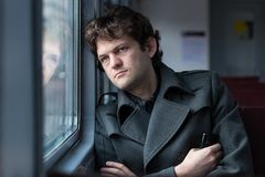 Ταξίδι με το τραίνο Λυπημένο άτομο που ταξιδεύει με το τραίνο, που κοιτάζει μέσω του παραθύρου και που σκέφτεται για την απλήρωτη Στοκ Εικόνα