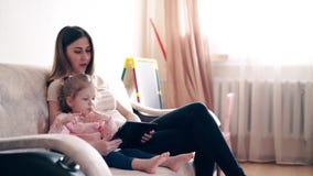 Ταξίδι, 4k: Η νέα ελκυστική μητέρα και η γλυκιά κόρη κάθονται στον καναπέ απόθεμα βίντεο