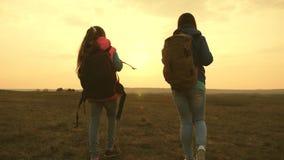 Ταξίδι Mom και κορών με ένα σακίδιο πλάτης ενάντια στον ουρανό η μητέρα και το παιδί τουριστών πηγαίνουν στο ηλιοβασίλεμα στα βου απόθεμα βίντεο