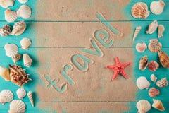 Ταξίδι λέξης που γράφεται στην άμμο μεταξύ των θαλασσινών κοχυλιών Στοκ εικόνα με δικαίωμα ελεύθερης χρήσης