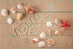 Ταξίδι λέξης που γράφεται στην άμμο μεταξύ των θαλασσινών κοχυλιών Στοκ Φωτογραφίες