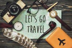 Ταξίδι αφήστε ` s να πάει έννοια σημαδιών κειμένων ταξιδιού στο χάρτη wanderlust ισχίο Στοκ Εικόνες