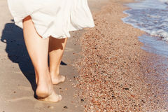 Ταξίδι διακοπών - κινηματογράφηση σε πρώτο πλάνο ποδιών γυναικών που περπατά στην άσπρη χαλάρωση άμμου στο κάλυψη-επάνω pareo παρ Στοκ Φωτογραφία