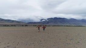 Ταξιδιωτικά τρέξιμο και χαρωπά κύμα τα όπλα τους οι τουρίστες τύπων και κοριτσιών είναι ευτυχείς απόθεμα βίντεο