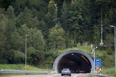 Ταξιδιωτικοί άνθρωποι που οδηγούν το αυτοκίνητο στο περασμένο δρόμος βουνό στη σήραγγα αυτοκινήτων Στοκ φωτογραφίες με δικαίωμα ελεύθερης χρήσης