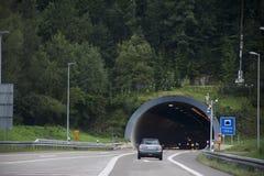 Ταξιδιωτικοί άνθρωποι που οδηγούν το αυτοκίνητο στο περασμένο δρόμος βουνό στη σήραγγα αυτοκινήτων Στοκ Φωτογραφίες