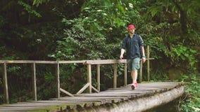 Ταξιδιωτικοί σταυροί μέσω της ένωσης της γέφυρας στο πράσινο θερινό δάσος φιλμ μικρού μήκους