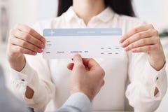 Ταξιδιωτικός πράκτορας που παρουσιάζει εισιτήριο πτήσης στον πελάτη στοκ φωτογραφίες με δικαίωμα ελεύθερης χρήσης