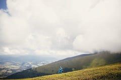 Ταξιδιωτικό hipster κορίτσι στο μπλε αδιάβροχο με το σακίδιο πλάτης, εξερεύνηση Στοκ Εικόνες