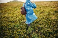 Ταξιδιωτικό hipster κορίτσι στο μπλε αδιάβροχο με το σακίδιο πλάτης, εξερεύνηση Στοκ Φωτογραφία